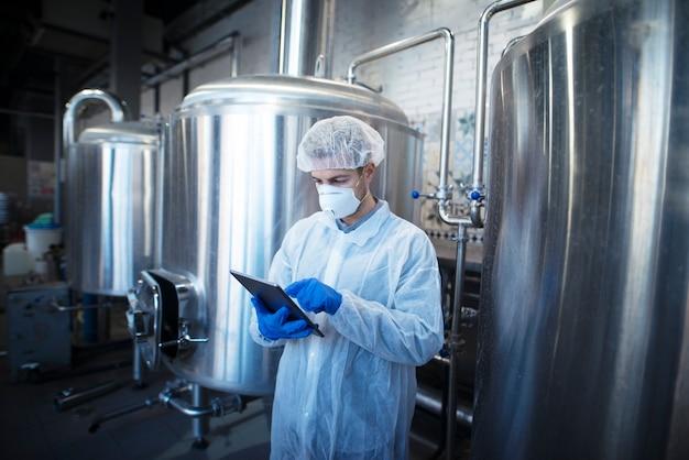 Een ervaren technoloog in wit beschermend uniform die tablet vasthoudt en de voedselproductie controleert in de verwerkingsfabriek Gratis Foto