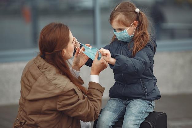 Een europese moeder in een gasmasker met haar dochter staat in de buurt van een gebouw. de ouder leert haar kind hoe ze een beschermend masker moeten dragen om zichzelf te beschermen tegen virussen Gratis Foto