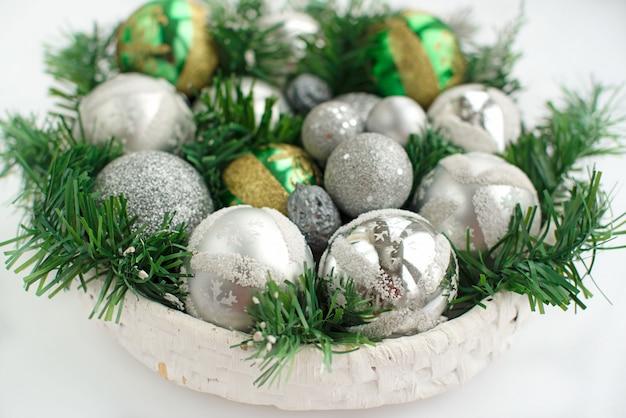 Een feestelijk kerstarrangement kunstmatige takken, glazen bollen in de mand. Premium Foto