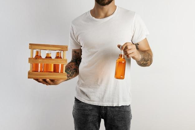 Een feestgastheer in een effen katoenen t-shirt en een donkere spijkerbroek met een pakje ambachtelijk fruitbier en een geïsoleerd op wit Gratis Foto