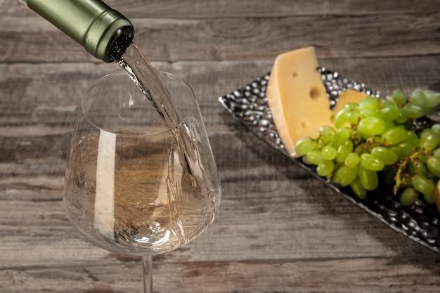 Een fles en een glas witte wijn met fruit over houten tafel Gratis Foto