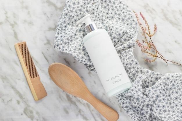Een fles met douchegel, een borstel en een haarkam met een stuk stof met bloemen op een marmeren tafel Premium Foto