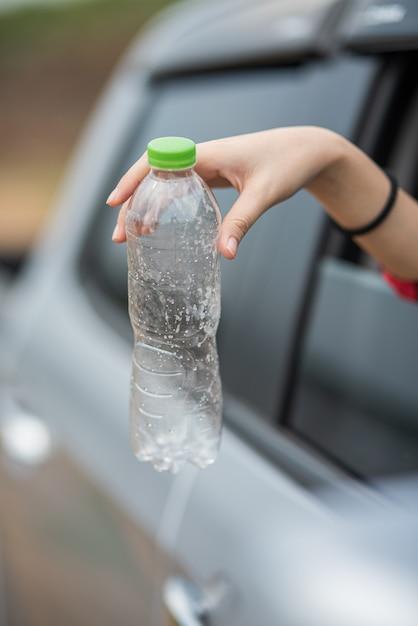 Een fles water vasthouden en de auto uitsteken. Gratis Foto