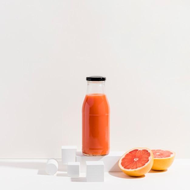 Een flesje vers rood sinaasappelsap Gratis Foto