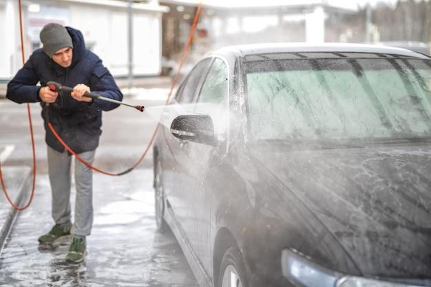 Een foto van een man die een auto wast onder hoge waterdruk buiten in het koude seizoen. Premium Foto