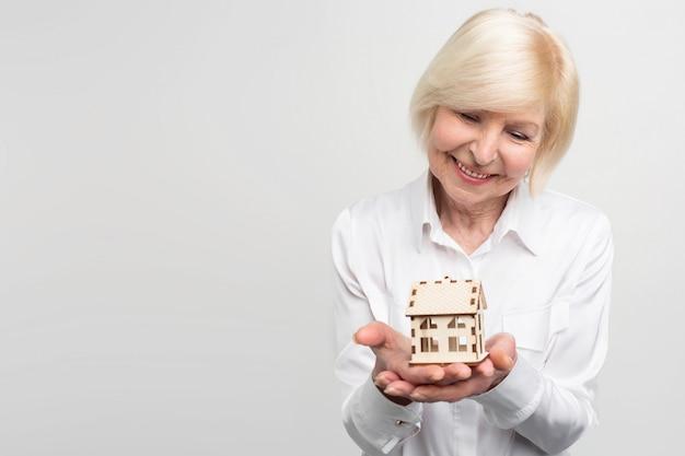 Een foto van een vrouw met een klein speeltje in haar hand. ze is oud en wil de rest van haar leven een aantal garanties hebben. Premium Foto