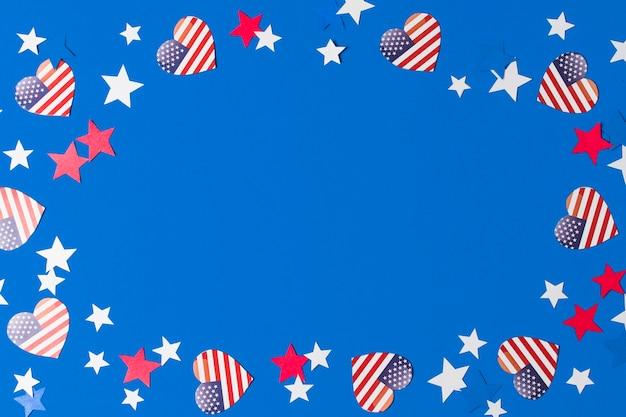 Een frame gemaakt met hart vorm amerikaanse vlaggen en sterren voor het schrijven van de tekst op een blauwe achtergrond Gratis Foto