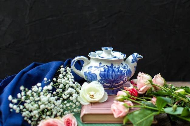 Een front close-up bekijken witte blauwe ketel rond blauw weefsel en verschillende gekleurde rozen op de donkere vloer Gratis Foto