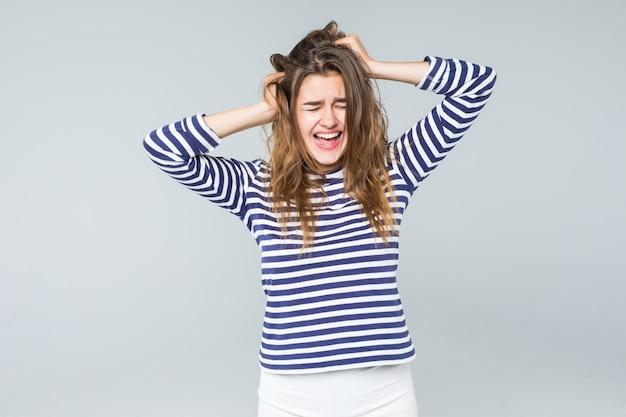 Een gefrustreerde en boze vrouw schreeuwt hardop en trekt haar haar dat op witte achtergrond wordt geïsoleerd Gratis Foto