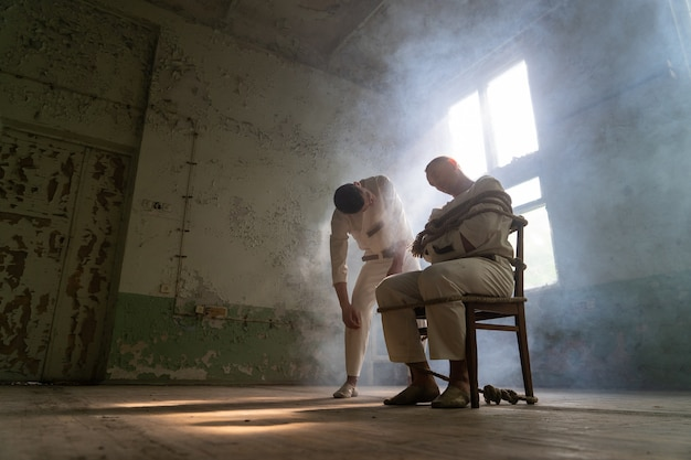 Een gekke man in een keurslijf is vastgebonden op een stoel in een verlaten oude kliniek en de andere krankzinnige man komt geïnteresseerd dichterbij. Premium Foto