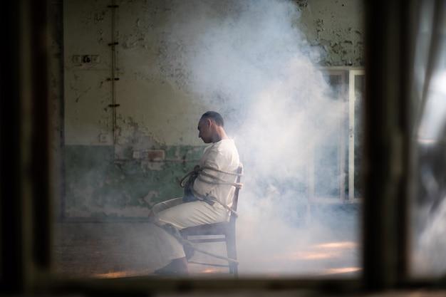 Een gekke man in een keurslijf zit vastgebonden op een stoel in een verlaten oude kliniek. Premium Foto