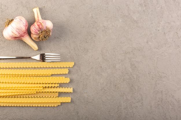Een gele droge lange italiaanse deegwaren van hoogste mening ruwe deegwaren samen met knoflook en vork die op de grijze maaltijd van het achtergrondgroentenvoedsel wordt geïsoleerd Gratis Foto