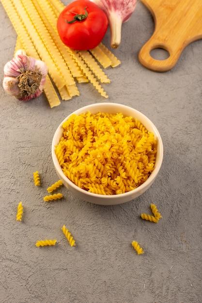 Een gele droge lange italiaanse deegwaren van hoogste menings ruwe deegwaren samen met knoflook en rode tomaten en vork die op de grijze maaltijd van het achtergrondgroentenvoedsel wordt geïsoleerd Gratis Foto
