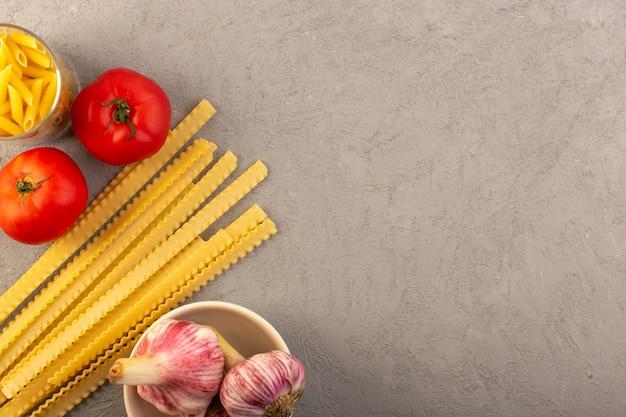 Een gele droge lange italiaanse deegwaren van hoogste menings ruwe deegwaren samen met rode tomaten en knoflook dat op de grijze maaltijd van het achtergrondgroentenvoedsel wordt geïsoleerd Gratis Foto