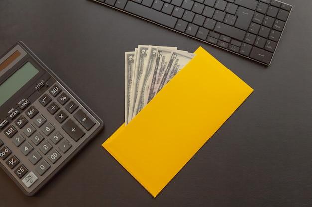 Een gele envelop met geld op een donker lederen bureau, naast een rekenmachine en een toetsenbord. Premium Foto