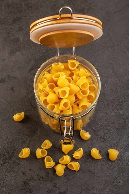 Een gele ruwe binnenkantkom van vooraanzicht italiaanse droge deegwaren die op dark wordt geïsoleerd Gratis Foto