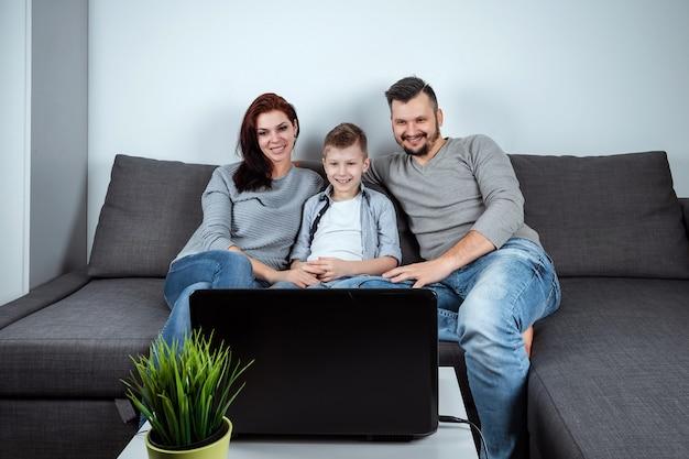 Een gelukkig gezin met een glimlach die iets in een laptop bekijkt Premium Foto