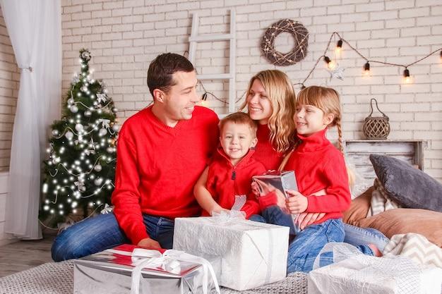 Een gelukkig gezin met geschenken met kerstmis Premium Foto