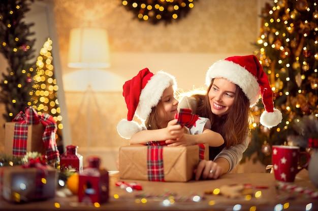 Een gelukkig gezin moeder en kind pack kerstcadeaus Premium Foto