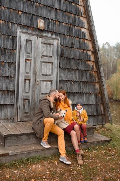 Een gelukkig gezin zit op de trap voor de ingang van het huis. Premium Foto