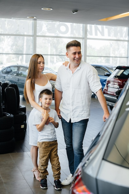Een gelukkig jong gezin kiest en koopt een nieuwe auto bij een autodealer. een nieuwe auto kopen. Premium Foto