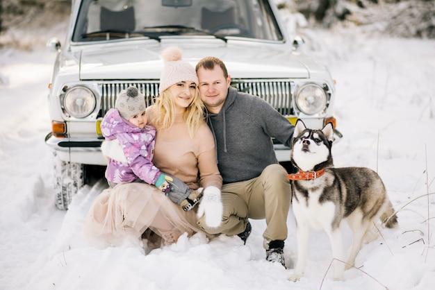 Een gelukkig jong gezin met een klein kind bereidt zich voor op kerstmis, wandelen met een husky hond op de achtergrond van een retro auto, op het dak van een kerstboom en geschenken in de winter besneeuwde bos. Premium Foto