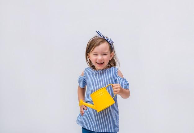 Een gelukkig meisje houdt een gieter en lacht op een geïsoleerd wit Premium Foto