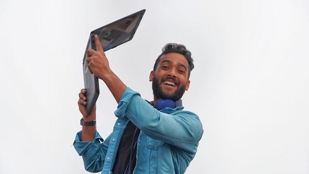 Een gelukkige jonge student met zijn laptop beurzenbeeld Premium Foto