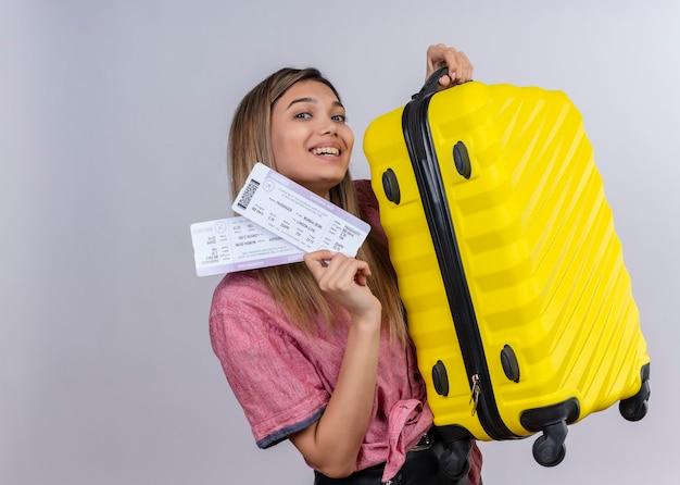 Een gelukkige jonge vrouw die rood overhemd draagt dat en vliegtickets en gele koffer glimlacht toont op een witte muur Gratis Foto