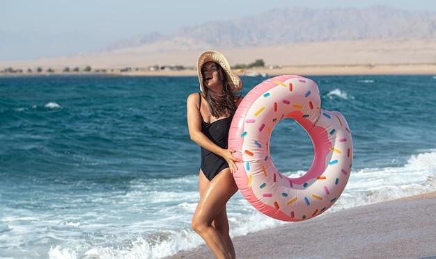 Een gelukkige jonge vrouw met een donutvormige zwemcirkel aan zee. het concept van vrije tijd en vermaak op vakantie. Gratis Foto