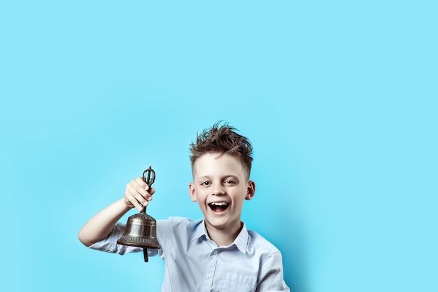 Een gelukkige jongen in een licht shirt gaat naar school. hij heeft een bel in zijn hand, die hij belt en lacht. Premium Foto