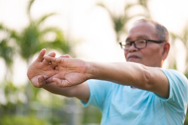 Een gelukkige oude mens die wapen uitrekken vóór openluchtoefening in een park Premium Foto