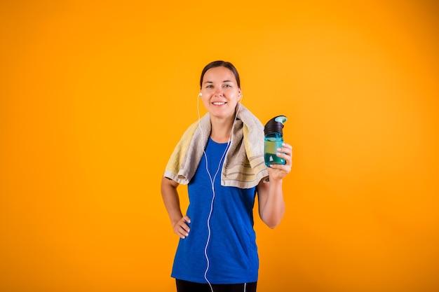 Een gelukkige vrouw in een sportuniform met een handdoek en een fles water op een oranje muur met een kopie van de ruimte Premium Foto