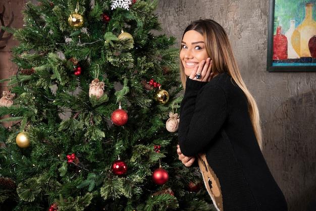 Een gelukkige vrouw in warme trui poseren in de buurt van de kerstboom. hoge kwaliteit foto Gratis Foto