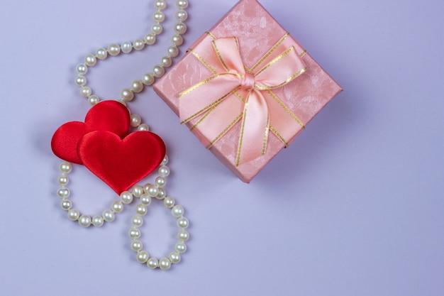 Een geschenk in een roze doos met parels en valentines op een paarse achtergrond. Premium Foto