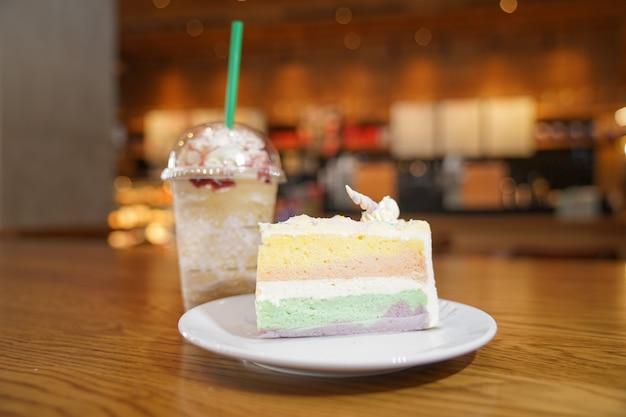 Een geschoven regenboogtaart versier met eenhoornhoorn bovenop naast koffiefrappe. de cake is in een witte schijf op de houten tafel Premium Foto