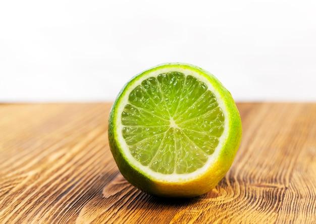 Een gesneden stuk zure groene limoen liggend op een bruine houten tafel. foto close-up. focus op fruit Premium Foto