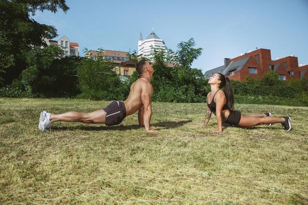 Een gespierde atleten training in het park. gymnastiek, training, flexibiliteit van fitnesstraining. zomerstad in zonnige dag op ruimteveld Gratis Foto