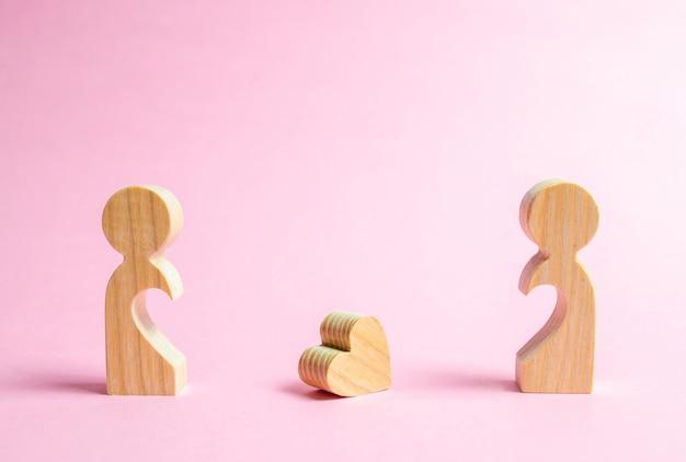 Een gevallen hart ligt tussen twee voormalige geliefden. Premium Foto
