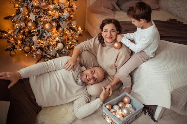 Een gezin met een kind thuis in de slaapkamer bij het bed bij de kerstboom. Premium Foto