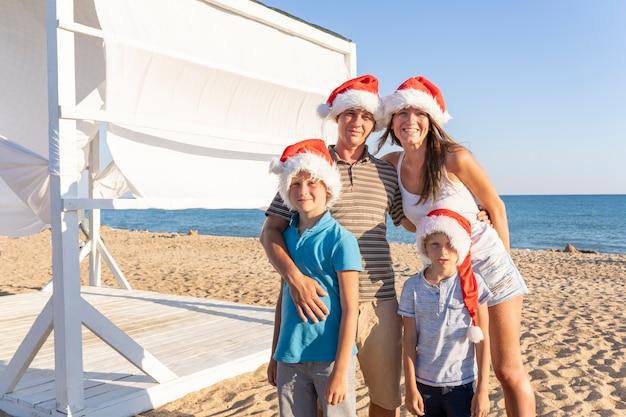 Een gezin van vier, moeder, vader en twee kinderen in kerstman hoeden in zandstrand aan zee. gelukkig kerstfeest familie vieren het nieuwe jaar aan de kust. Premium Foto