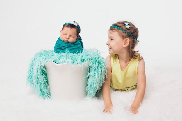Een gezonde levensstijl, de bescherming van kinderen, winkelen - een tiener met een pasgeboren baby die samen speelt. gelukkige jonge geitjes: broer en zus op witte achtergrond Premium Foto