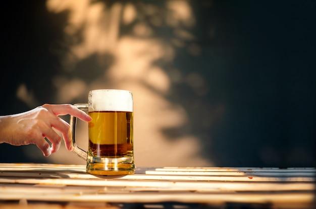 Een glas bier op tafel in zonnige zomerdag. mensen die brouwen drinken Premium Foto