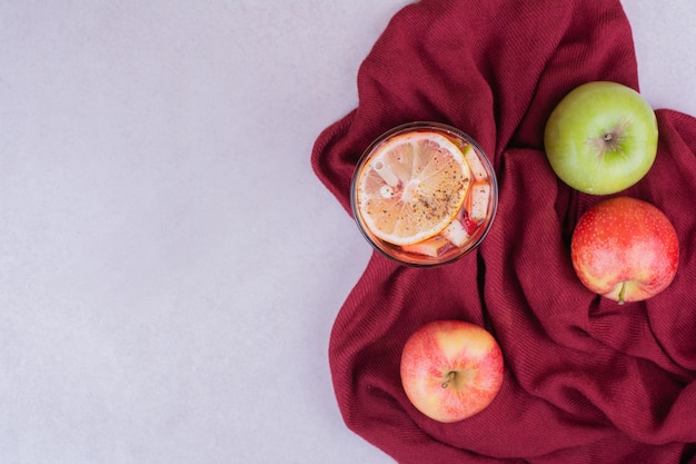 Een glas drank met rode en groene appels Gratis Foto