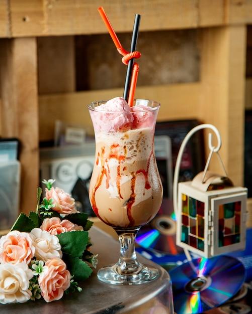 Een glas ijskoffie drinken gegarneerd met zoete katoen in roze Gratis Foto