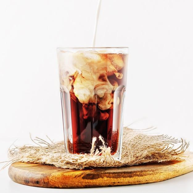 Een glas ijskoffie met room op wit gieten Premium Foto