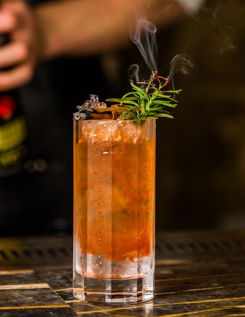 Een glas kleurrijke koude drank met rozemarijnbladeren en ijsblokjes. Gratis Foto