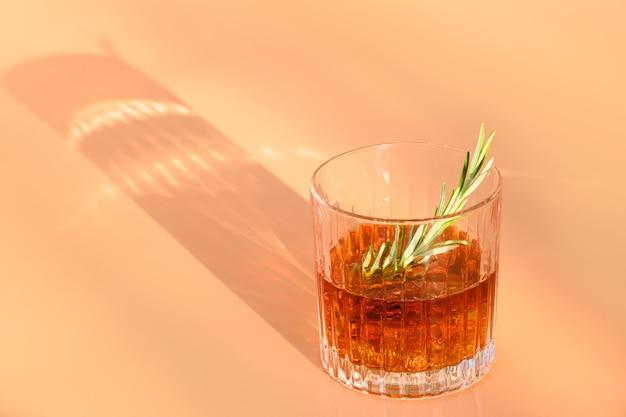 Een glas koude whisky versiert rozemarijn op beige achtergrond met zonnige schaduw. Premium Foto