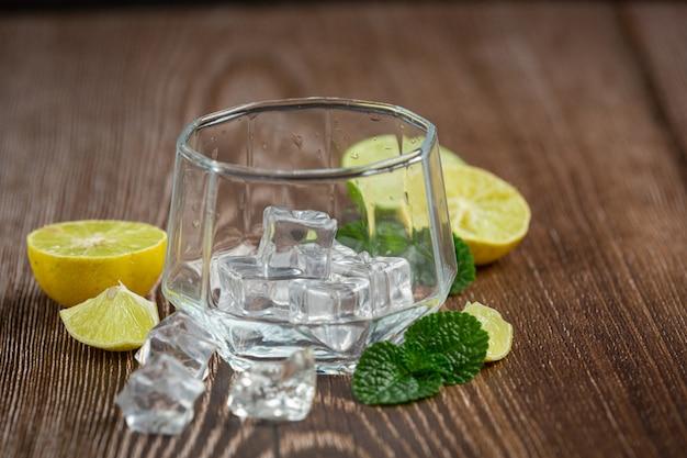 Een glas met ijs wordt op tafel gezet. Gratis Foto