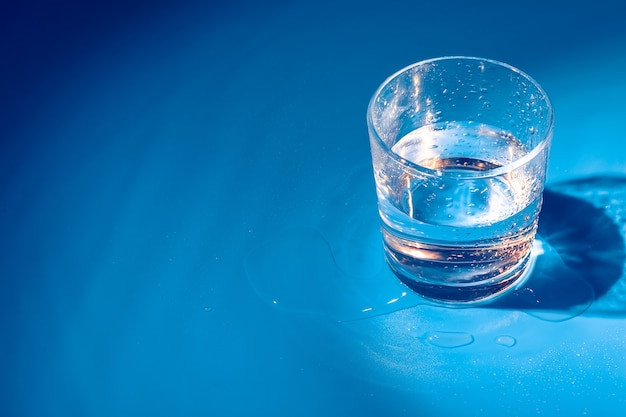 Een glas met waterdalingen op een donkerblauwe achtergrond sluit omhoog Premium Foto